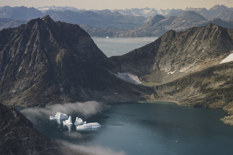 Icebergs floating on the water with much larger mountains in the background.