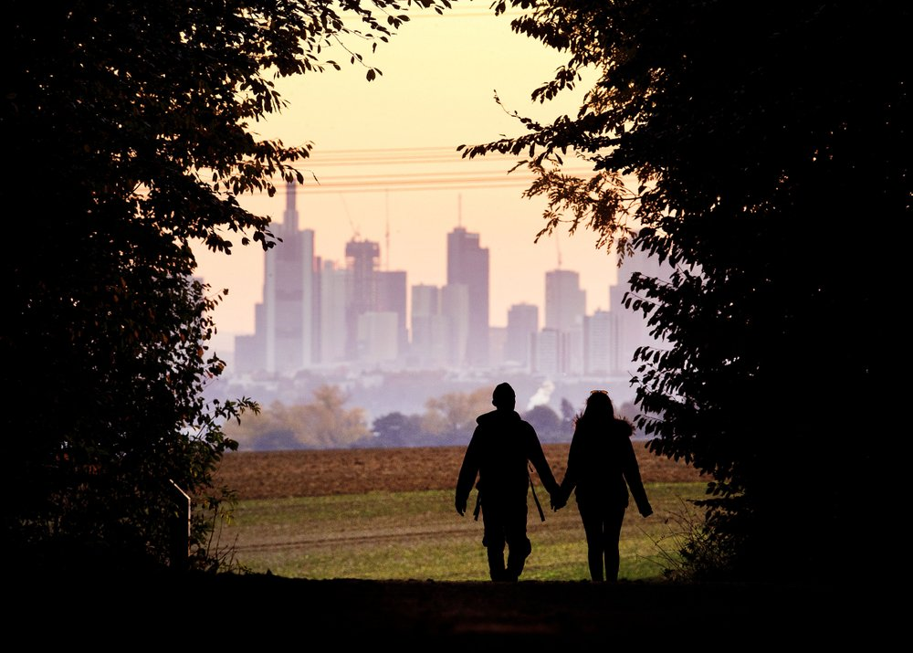 A couple walking out of a forest and into a field in front of a city.