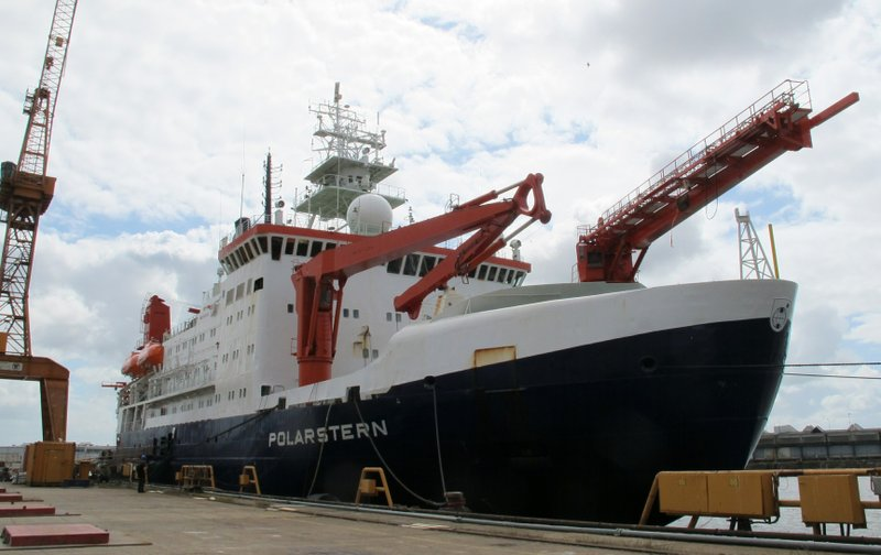 A boat next to a dock with a crane. The side of the boat reads Polarstern.