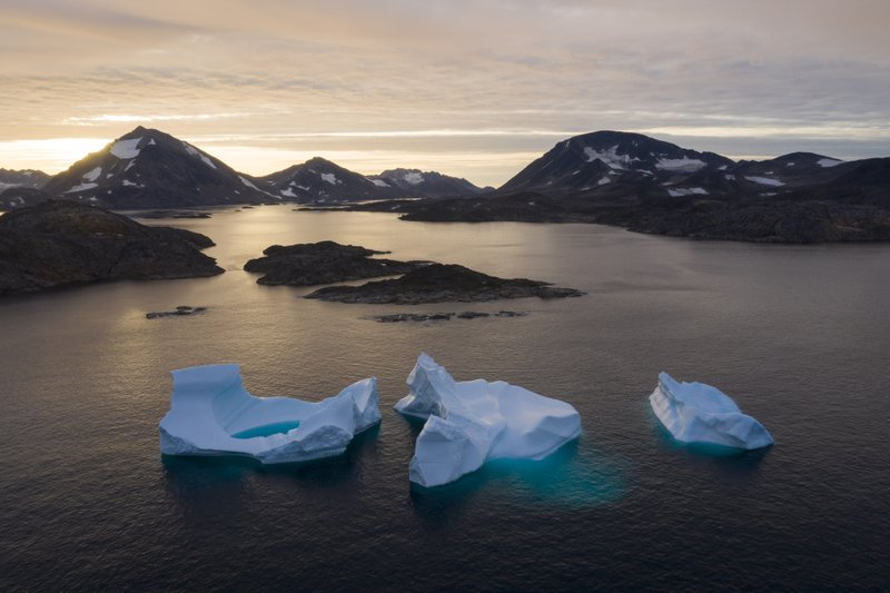 Icebergs floating on the ocean with mountains in the background.