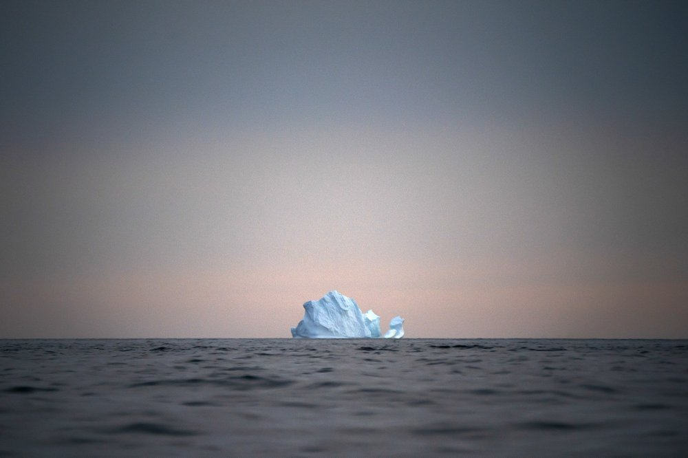 An iceberg floating on the ocean with a sunset in the background.