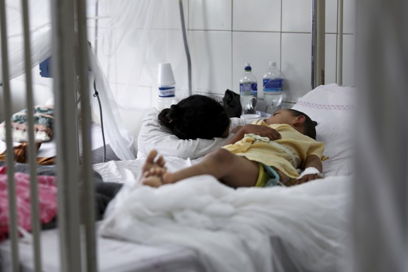 A woman hugging a child lying in a hospital bed.