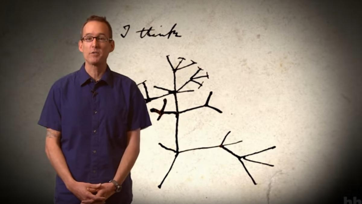 Educator standing in front of an phylogenetic tree diagram