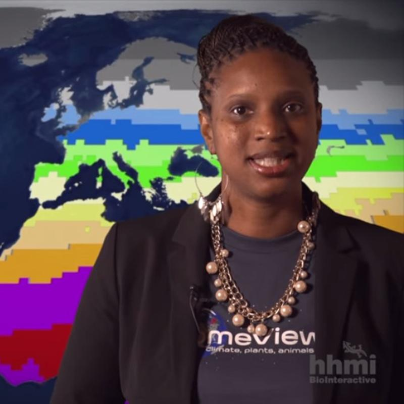 Kenyatta McKie in front of a map showing global UV radiation patterns.