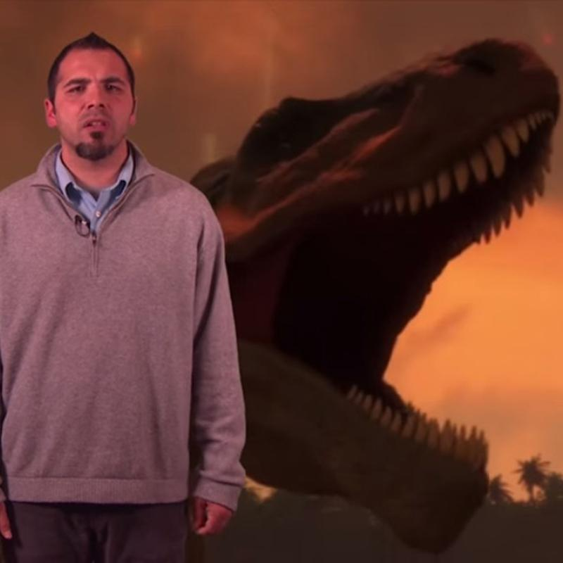 Chris Monsour in front of an image of a dinosaur